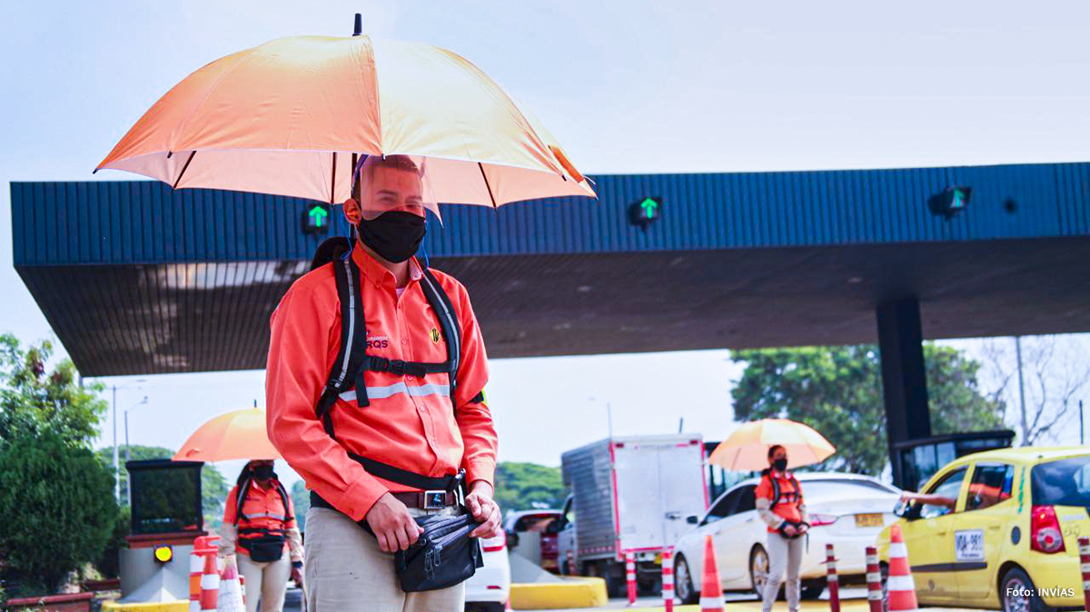 Fotografía de trabajador del INVÍAS en su trabajo de recaudación de peajes bajo la lluvia.