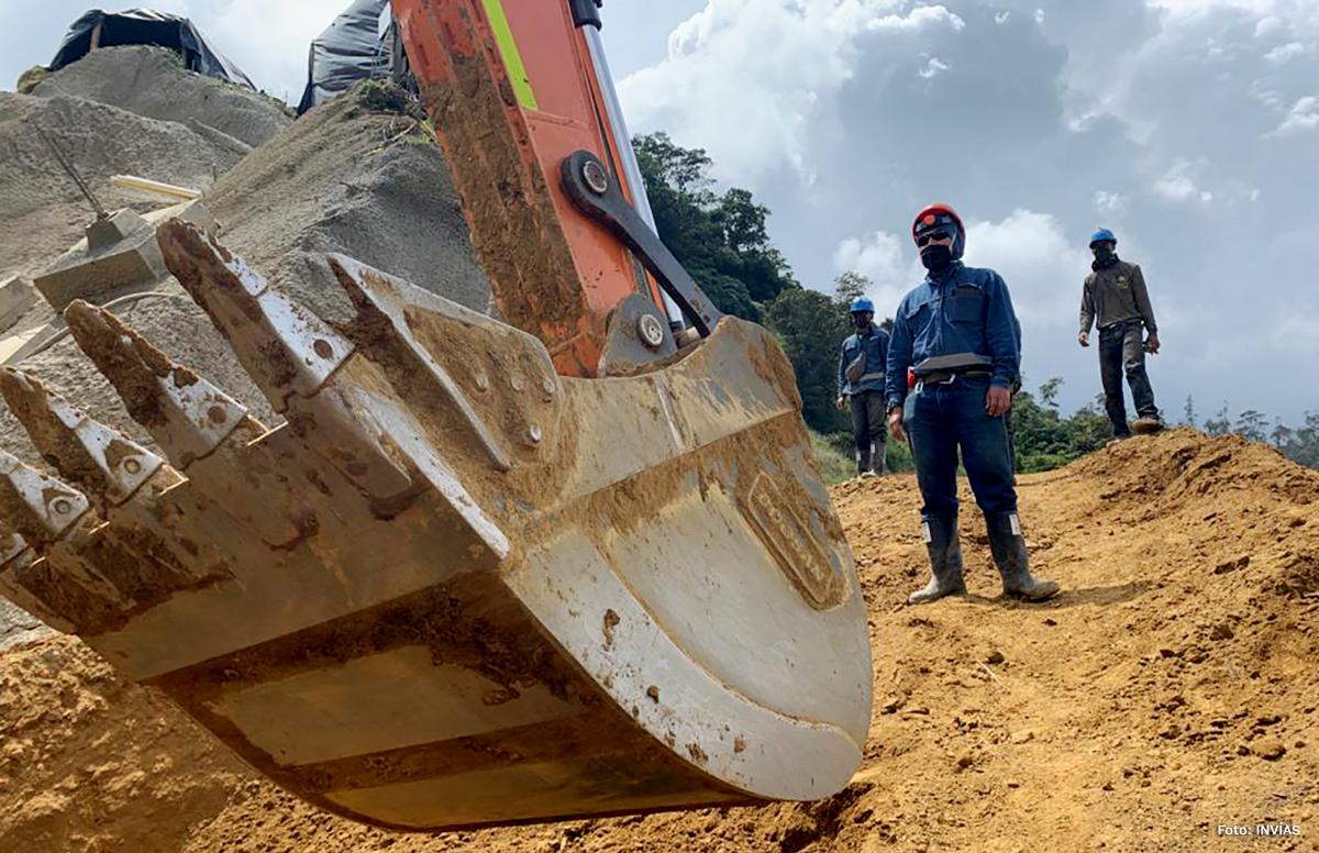 Fotografía de trabajador del INVÍAS en la montaña junto a máquina de trabajo pesado.